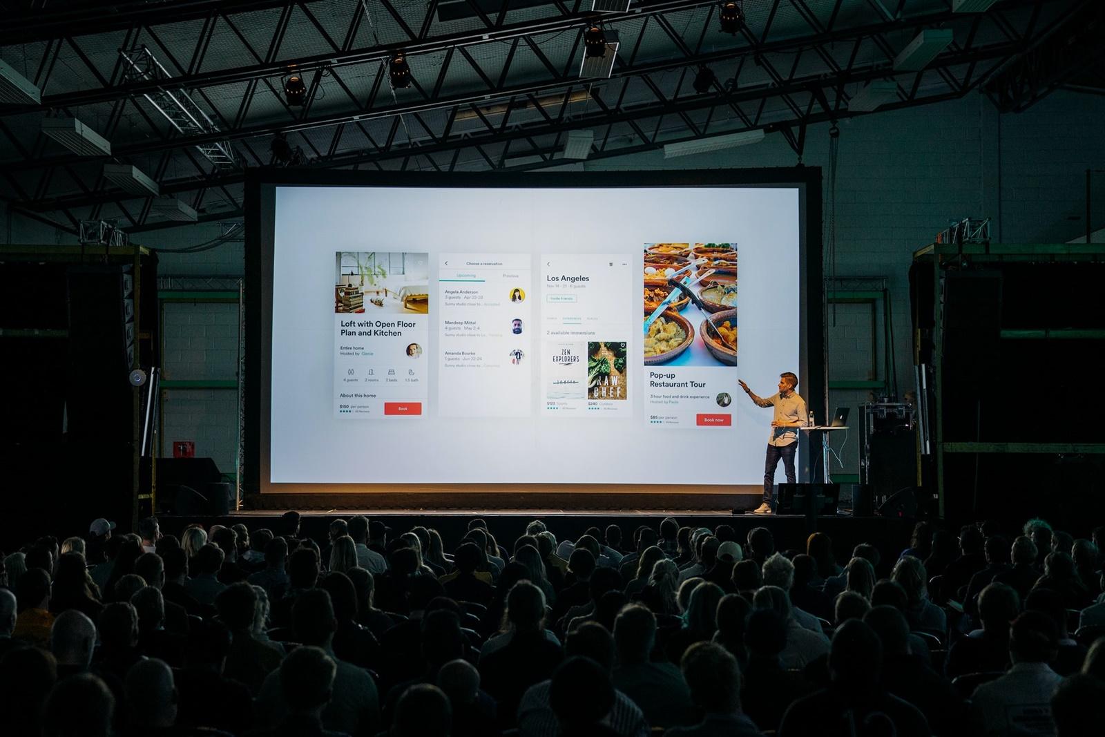 Homem em palco faz apresentação sobre airbnb