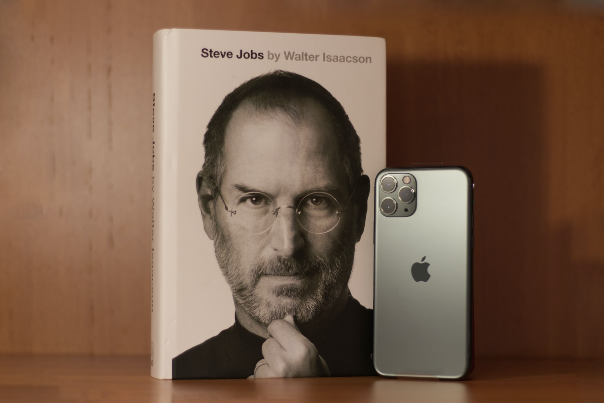Mesa com livro de Steve Jobs e Iphone